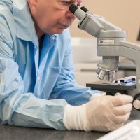 lab tech reviews sample under microscope (lab services)